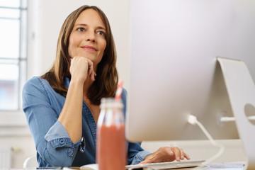 zufriedene mitarbeiterin im büro schaut auf ihren computer