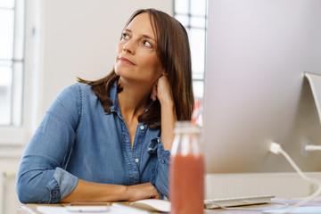 nachdenkliche frau sitzt im büro am schreibtisch und schaut zur seite