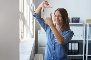 frau im büro bildet eine rahmen mit den händen
