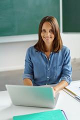lehrerin sitzt am schreibtisch in der klasse und arbeitet am laptop