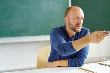 lehrer deutet mit der hand nach vorne in richtung klasse