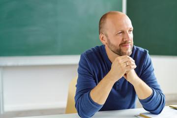entspannter lehrer sitzt im klassenzimmer