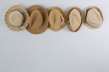 Various straw hats hanging on hook