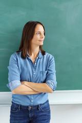 lehrerin steht mit verschränkten armen vor der tafel und schaut zur seite
