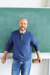 lehrer steht im klassenzimmer vor der tafel