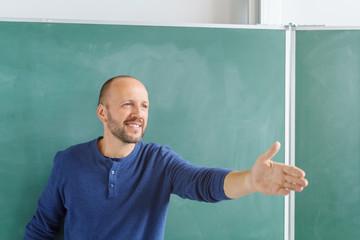 motivierter lehrer zeigt mit der hand nach vorne in die klasse