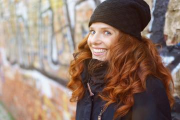 lachende frau mit mütze und warmer jacke steht draußen in der stadt