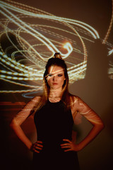 Abstract portrait of a beautiful girl in the light of the projector. Warm orange shades. Light bulb Edison. A feeling of warmth. A sense of fragility and beauty. Plastic body. Beautiful and mysterious