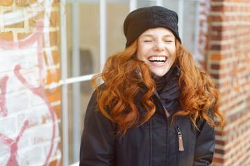 lachende frau steht draußen in der kälte