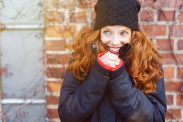 lachende frau steht draußen in der kält und wärmt sich die hände
