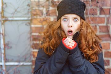 frau mit mütze und winterjacke macht ein überraschtes gesicht