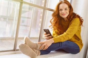 frau sitzt gemütlich zuhause am fenster mit ihrem mobiltelefon