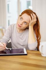 grafikerin arbeitet zuhause am tablet und stützt nachdenklich den kopf auf