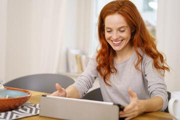 attraktive frau sitzt in ihrem wohnzimmer und schaut lachend auf ihr tablet