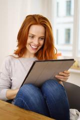 glückliche frau sitzt zuhause in ihrer wohnung und liest am tablet