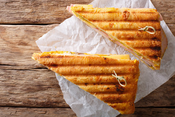 Freshly cooked grilled sandwich with meat and cheese, close-up on paper on the table. horizontal top view
