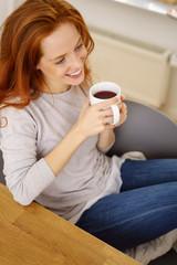 lächelnde frau sitzt zuhause am tisch und genießt eine tasse tee