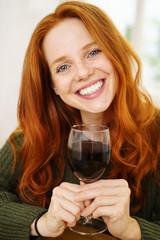 attraktive frau mit roten haaren hält ein glas wein in der hand