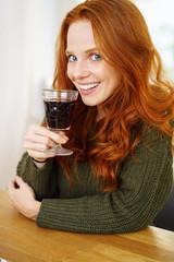 lächelnde frau trinkt ein glas rotwein
