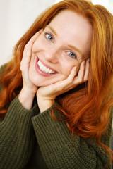 lächelnde frau mit grünem strickpullover und langen roten haaren
