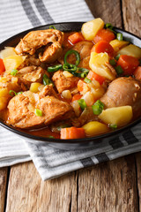 Spicy chicken stew with vegetables close-up on the table. vertical