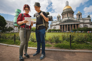 Young tourists check the route on the paper map near Kazan Kathedral of Saint Petersburg, Russia