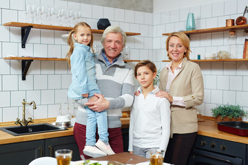 Happy grandparents and adorable grandchildren in the kitchen at home