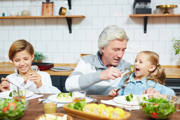 Grandfather feeding his little granddaughter with boiled broccoli by festive table or by breakfast
