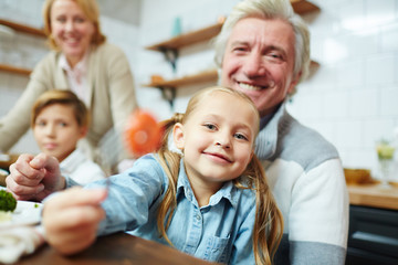 Adorable girl on grandfather hands looking at camera by table during family breakfast