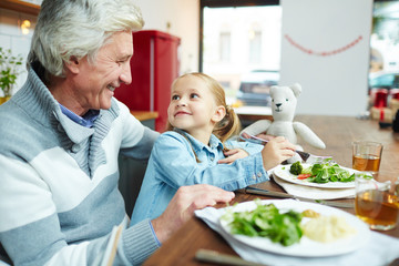 Cute girl eating organic food and talking to her grandfather by breakfast