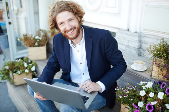 Businessman looking at camera with smile while browsing in the net outdoors