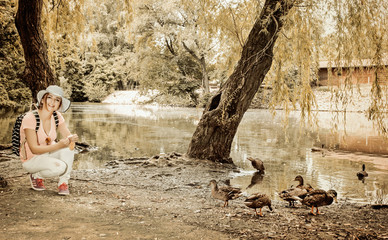 Woman is feeding the group of duck in park, vintage filter