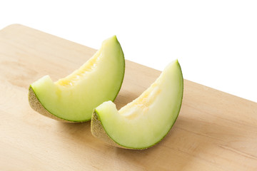 2 slices japanese melons on a wooden cutting board