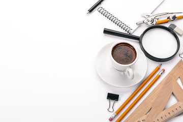 Office desktop. Magnifier, notepad, pen, cup of coffee. On a white background. Top view. Free space for text.