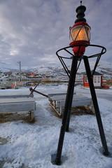 Harbor lantern upon metal tripod-picnic tables. Lodingen fishin port-Hinnoya-Lofoten-Norway. 0661