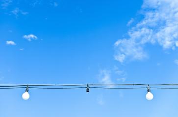 Light bulbs hang out on the blue sky