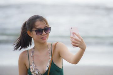 young pretty and sweet Chinese Asian woman on the beach taking selfie picture portrait with mobile phone camera enjoying holiday happy