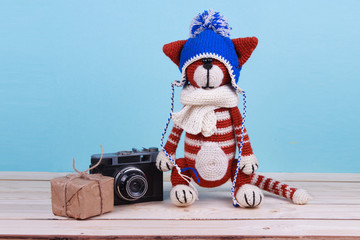 little red cat toy with vintage camera and box gift crochet handmade blue background