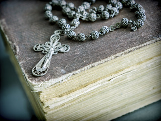 An ancient rosary on an old book