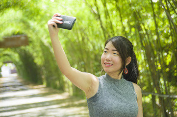 young pretty Chinese Asian woman enjoying having fun taking selfie picture with mobile phone camera posing cool