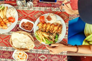 Woman eating Turkish chicken wing shish kebab in cafe, flat top view