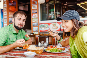 Man and woman tourists eat in the Turkish restaurant local cuisine and try kebabs