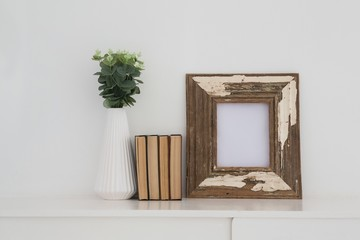 Wooden frame, vase and books arranged on table