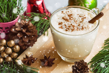 Eggnog, traditional drink for Christmas celebration party in glass topped with ground nutmeg and cinnamon stick, top view with copy space in Xmas theme decoration and snowfall effect background.