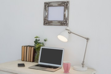 Electronic gadgets, lamp, book, mug, flora and book on table