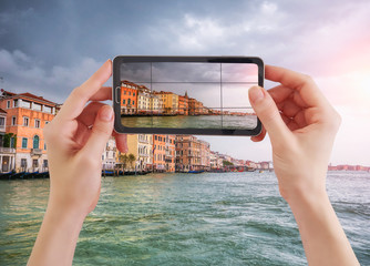 Woman taking photo of Canal Grande and venetian cityscape, Venice, Italy