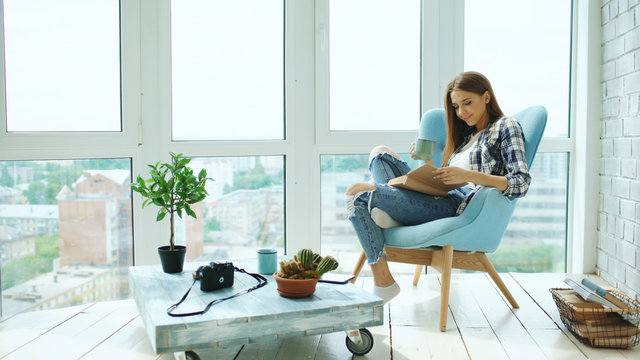 Young attractive woman read book and drink coffee sitting on balcony in modern loft apartment
