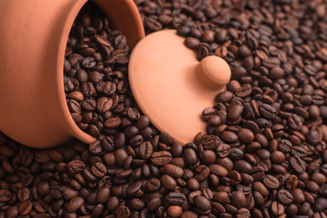 Clay pot and lid in coffee beans. Place for text or design.