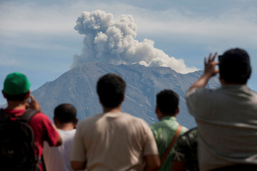 People watch as Mount Agung spews ash and smoke during an eruption from an obeservation post in Rendang, Karangasem, Bali