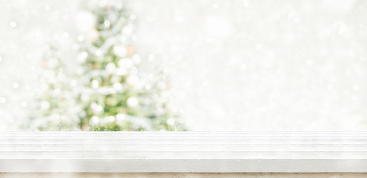 Empty white wooden table top with abstract muted blur christmas tree and snow fall background with bokeh light,Holiday backdrop,Mock up banner for display or montage of product